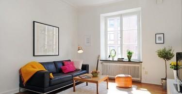 Чёрный диван в интерьере белой гостиной