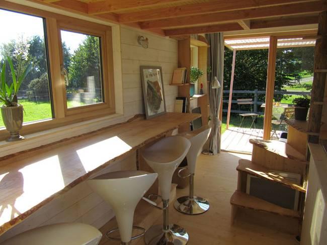 Дизайн дома на колёсах. Здесь есть длинный обеденный стол. Он соседствует с плитой в корпусе из древесины