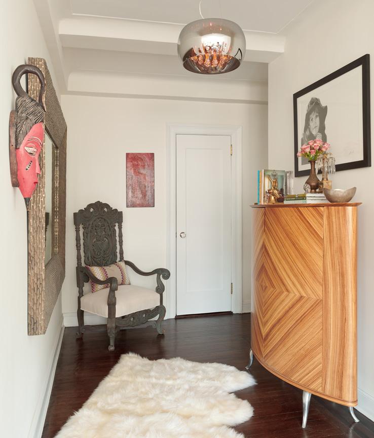Кресло в углу возле зеркала, картина и яркая африканская маска на стене