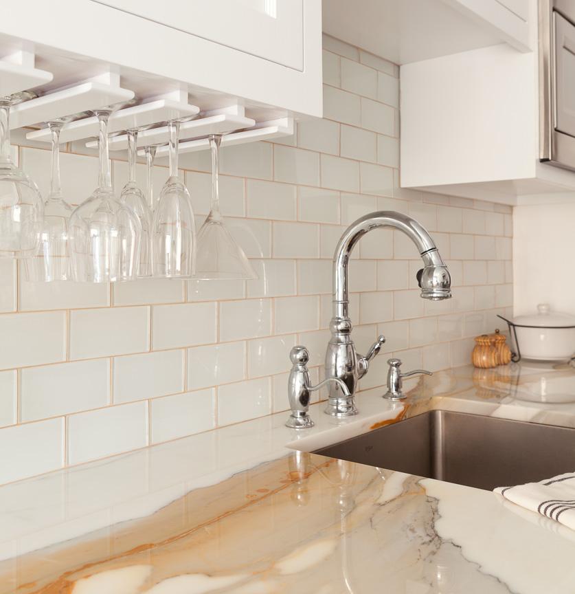 Кухонный кран, встроенный в мраморную столешницу, и подвешенные бокалы
