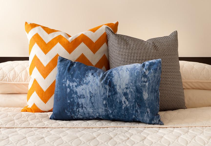 Яркие оранжевая, синяя и чёрно-белая декоративные подушки с интересными принтами на кровати