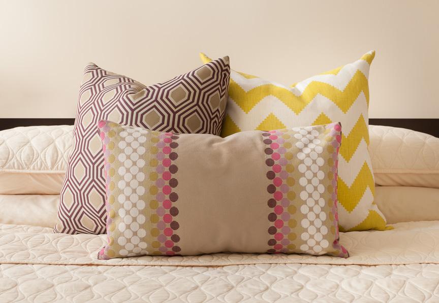 Яркие жёлтая и бежевые декоративные подушки с интересными принтами