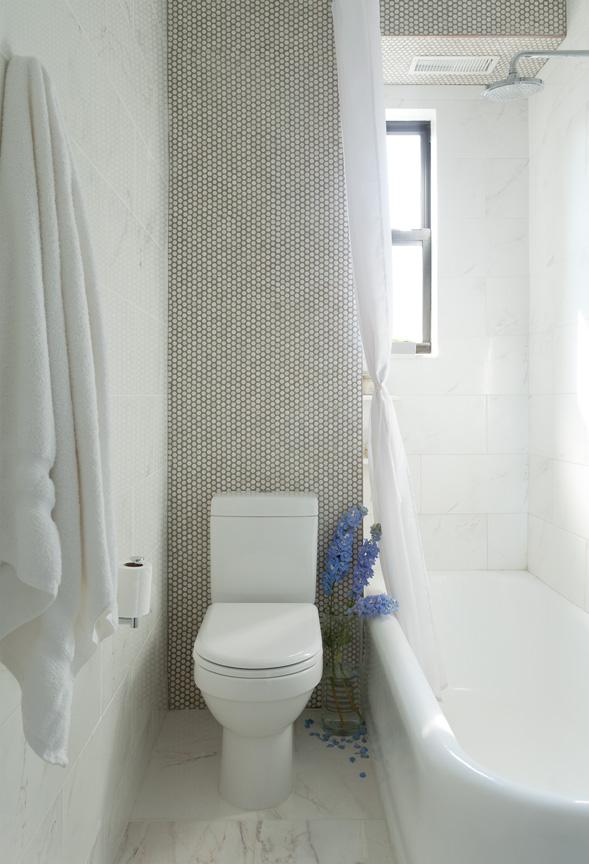 Белый унитаз и ванна в комнате, отделанной под мрамор