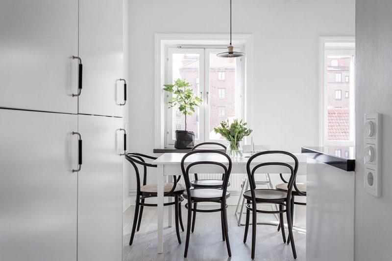 Чёрные стулья в белой столовой
