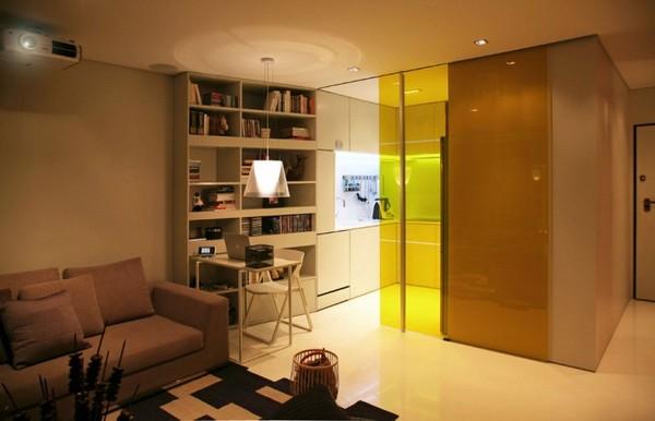 Кухня отделена стеклянной цветной перегородкой от пространства гостиной