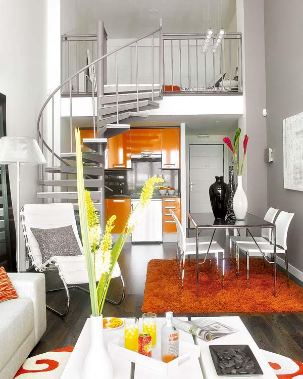 Интерьер квартиры с винтовой лестницей на второй уровень над кухней
