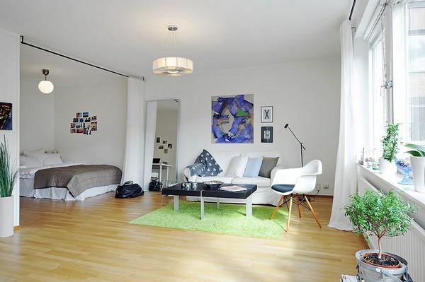 Интерьер квартиры с отделением пространства с кроватью белым занавесом от потолка до пола