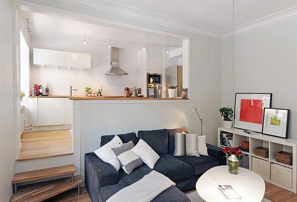 Кухня находится выше остального пространства квартиры и отделена глухой барной стойкой от гостиной