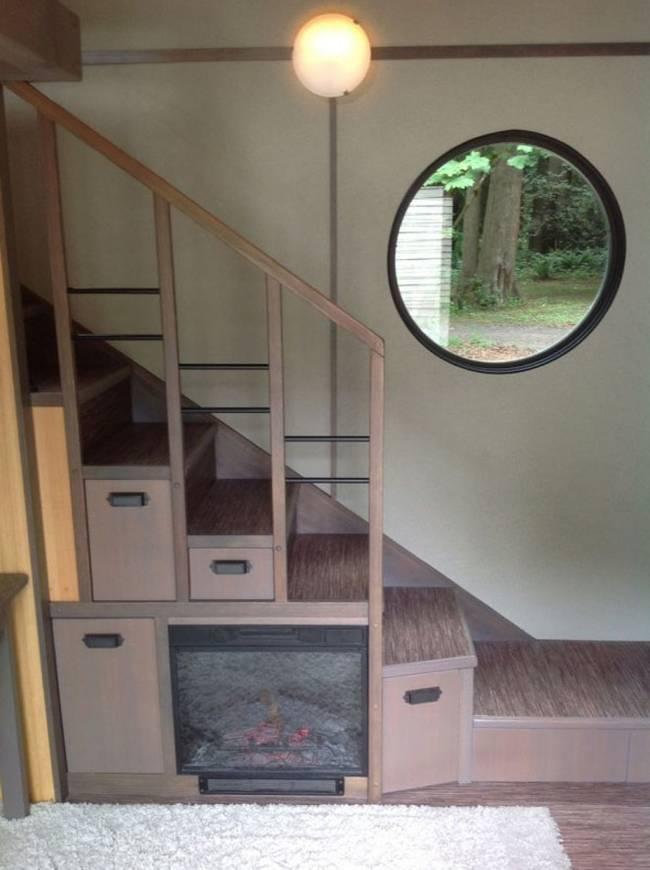 Электронный камин под лестницей в маленьком загородном домике