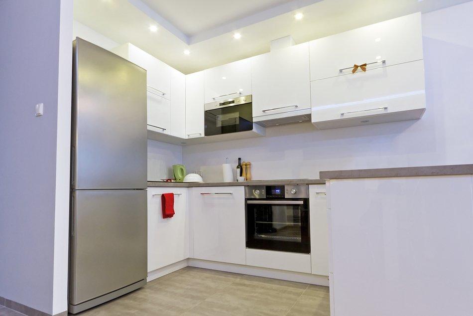 Белая кухня с серым холодильником