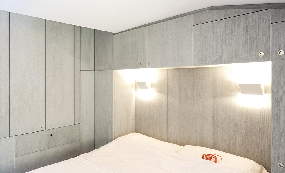 Большая кровать в спальне маленькой квартиры-студии