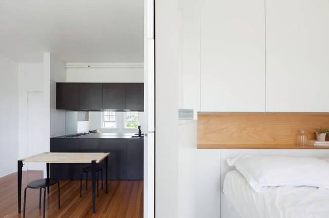 Модульная стена в интерьере квартиры: чёрная кухня и белоснежная спальня