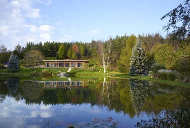 Небольшой дизайнерский дом. Фасад дома органично вписывается в ландшафт и красиво отражается в водной глади - фото 2