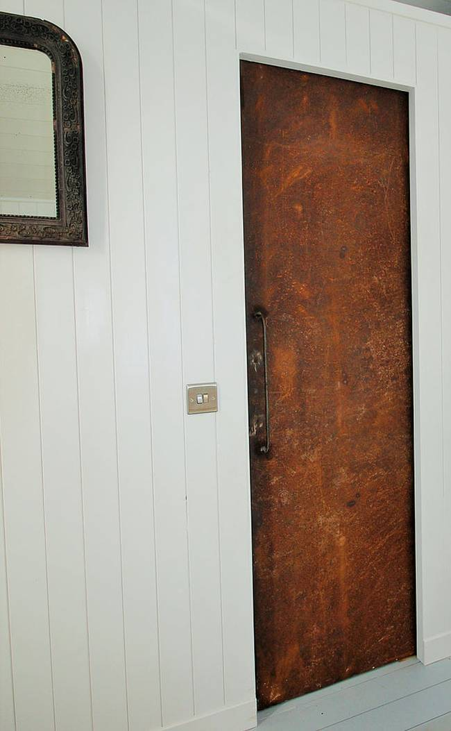 Интерьер хижины в лесу: жестяная дверь в ванную