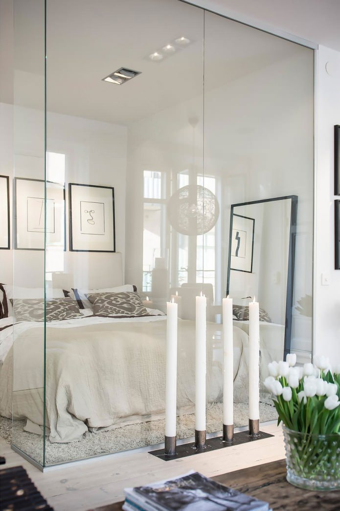 Спальня за стеклом квартиры-студии в скандинавском стиле