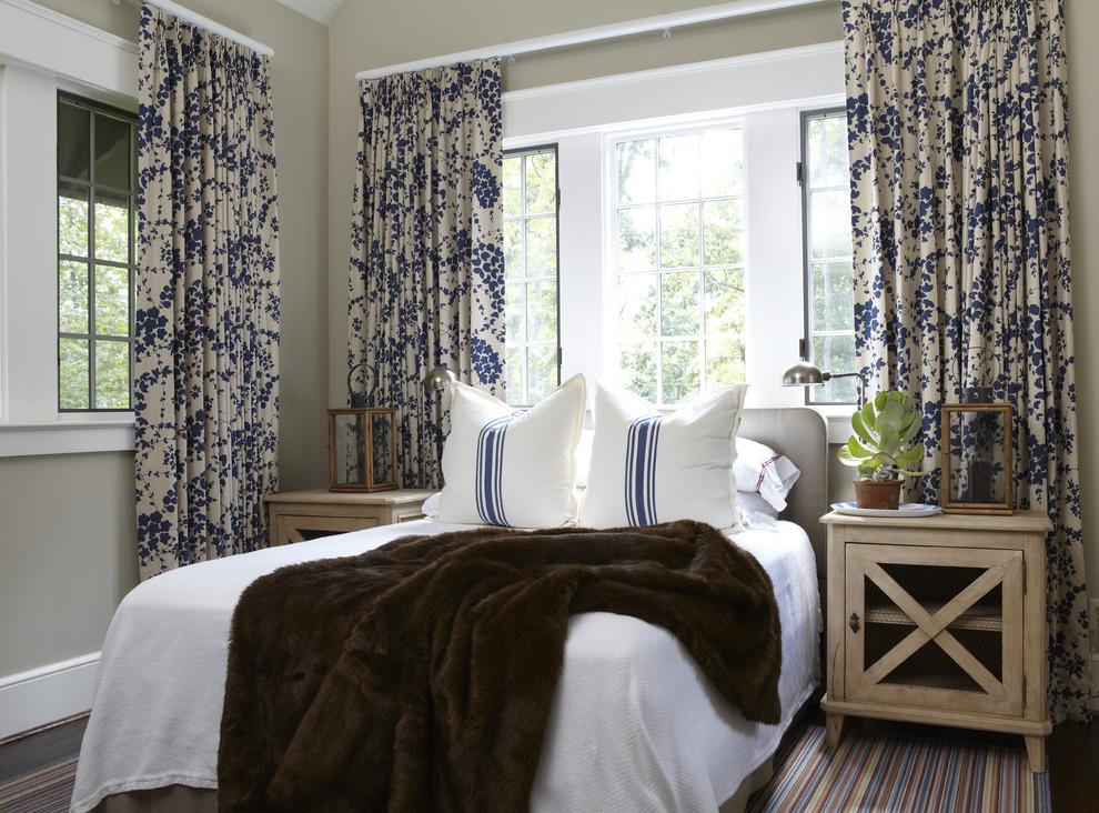 Синие цветы на шторах и полосы на подушках гармонично сочетаются в интерьере спальни