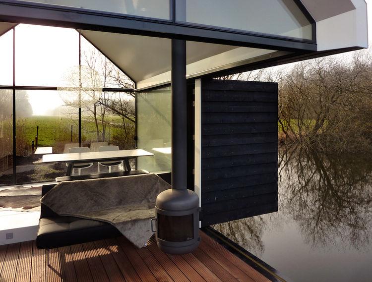 Терраса маленького стеклянного домика у озера в Голландии