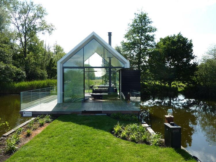 Маленький стеклянный домик у озера в Голландии