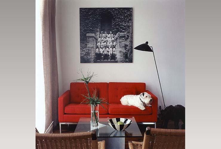 Строгий красный диван и плетёные кресла в гостиной
