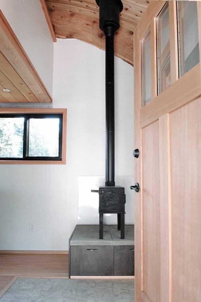 Интерьер дома на колёсах. Дровяная печка рядом со входом