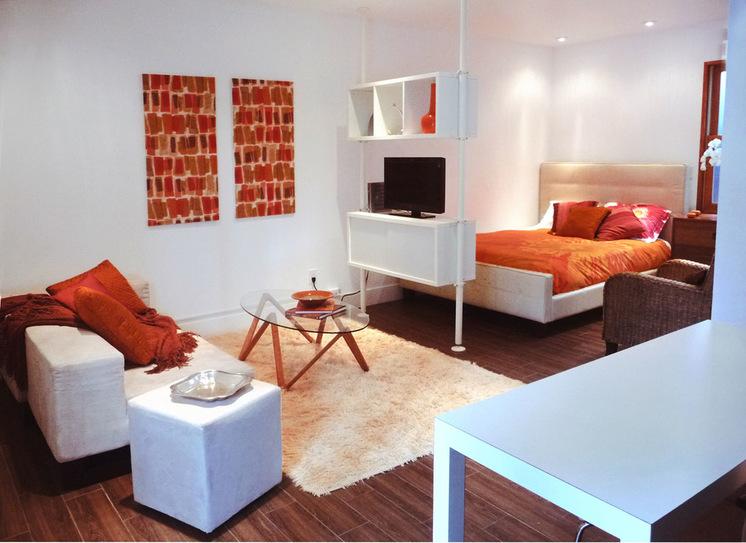 Интерьер белой квартиры-студии с оранжевыми акцентами