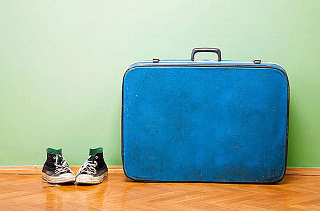 Кеды и чемодан в прихожей