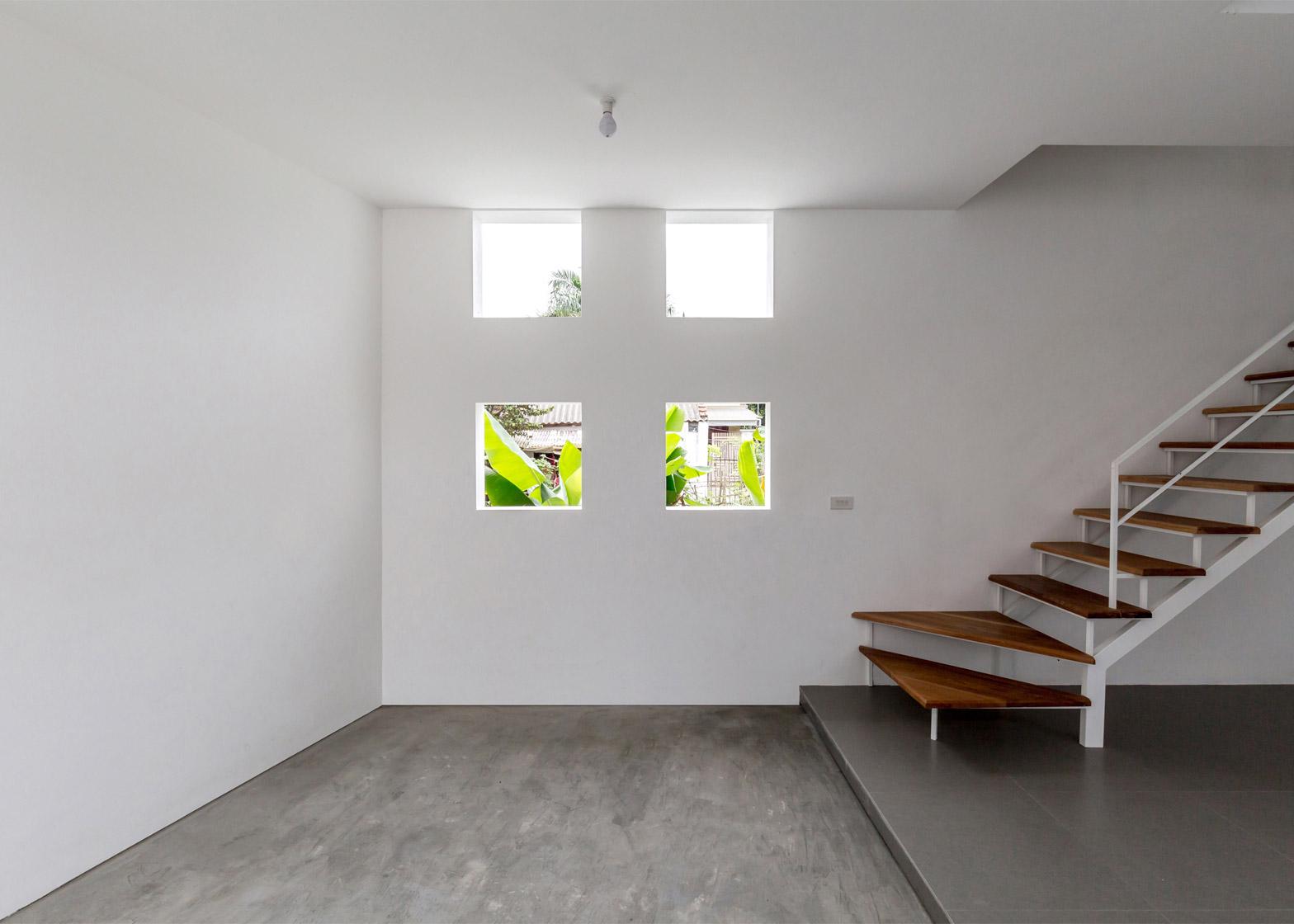 Маленькие окна в узком бетонном доме