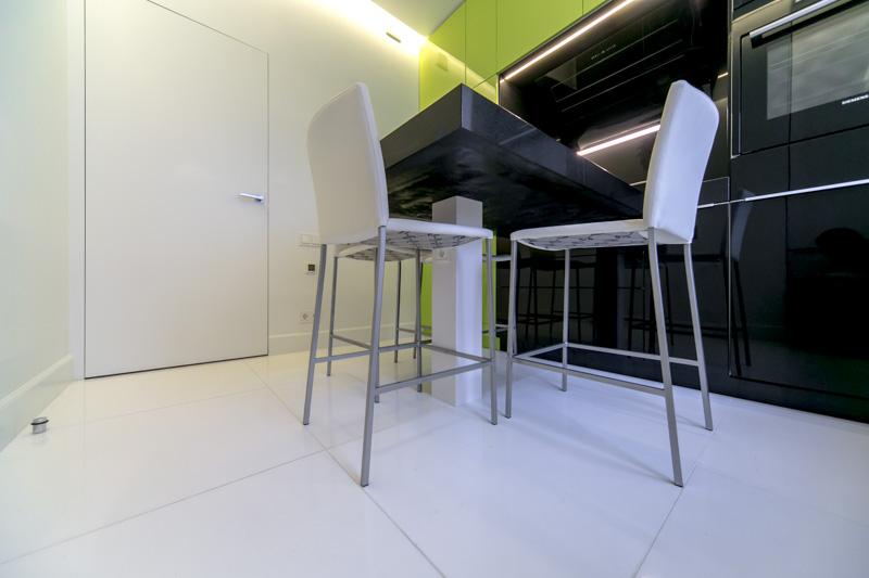 Белые стулья на фоне черно-салатовой кухни